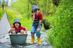 Leuke kinderen, jongens, die met boot en eenden spelen op een weinig riv royalty-vrije stock afbeelding