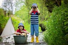 Leuke kinderen, jongens, die met boot en eenden spelen op een weinig riv Stock Afbeelding