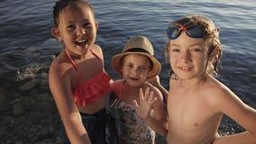 Leuke kinderen videopraatjes op smartphone op strand stock videobeelden