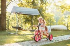 Leuke kleine blonde meisjes die een fiets in de zomer berijden Stock Foto's