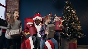 Leuke kleine jonge geitjes die de giften joying die van Santa Claus op de achtergrond van de Kerstmisboom krijgen stock footage
