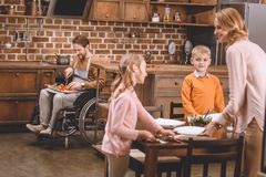 leuke kleine jonge geitjes met moeder dienende erachter lijst voor diner terwijl gehandicapte vader in rolstoel scherpe groenten stock foto's