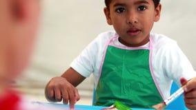Leuke kleine jongens die bij lijst in klaslokaal schilderen Stock Foto's