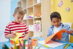 Leuke kleine jongens die document vormen in klaslokaal snijden stock foto's