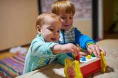 Leuke kleine jongens die met speelgoed door het huis spelen royalty-vrije stock afbeeldingen