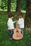 Leuke kleine kinderen die gitaar spelen Royalty-vrije Stock Afbeeldingen