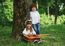 Leuke kleine kinderen die gitaar spelen Stock Foto's