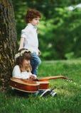 Leuke kleine kinderen die gitaar spelen Stock Afbeeldingen