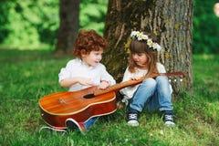 Leuke kleine kinderen die gitaar spelen Stock Afbeelding