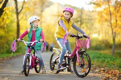 Leuke kleine zusters die fietsen in een stadspark berijden op zonnige de herfstdag Actieve familievrije tijd met jonge geitjes stock afbeeldingen