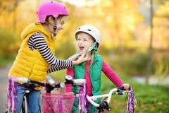 Leuke kleine zusters die fietsen in een stadspark berijden op zonnige de herfstdag Actieve familievrije tijd met jonge geitjes stock afbeelding