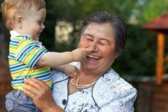 Leuke kleinzoon het grijpen neus van groot - grootmoeder Stock Afbeelding