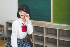 Leuke korte haired Aziatische meisjes Thaise mensen die glazen en Japanse schooluniformen dragen en onschuldig en leuk proberen t stock afbeeldingen