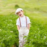 Leuke landbouwersjongen die zich in aardappelsrijen bevinden Royalty-vrije Stock Foto's