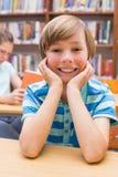 Leuke leerling die bij camera in bibliotheek glimlachen Stock Fotografie