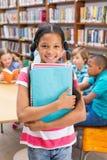 Leuke leerling die bij camera in bibliotheek glimlachen Stock Afbeelding