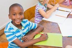 Leuke leerling die bij camera in klaslokaal glimlachen Royalty-vrije Stock Afbeelding