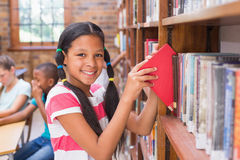 Leuke leerling die boeken in bibliotheek zoeken Royalty-vrije Stock Foto's