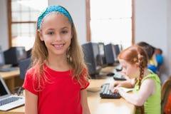 Leuke leerling die in computerklasse bij camera glimlachen stock afbeelding