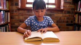Leuke leerling die een boek lezen bij de bibliotheek stock video