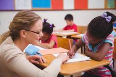 Leuke leerling die hulp van leraar in klaslokaal krijgen stock afbeeldingen