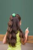 Leuke leerling die zich in klaslokaal bevinden die op bord schrijven Royalty-vrije Stock Afbeelding