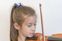 Leuke leerling het spelen viool in klaslokaal op de basisschool Meisje dat de viool speelt royalty-vrije stock foto's