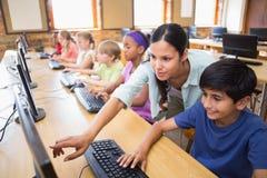 Leuke leerlingen in computerklasse met leraar Stock Foto's