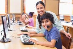 Leuke leerlingen in computerklasse met leraar Stock Foto