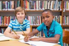 Leuke leerlingen die in bibliotheek trekken Stock Afbeeldingen