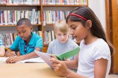 Leuke leerlingen die bij bureau in bibliotheek schrijven Royalty-vrije Stock Foto