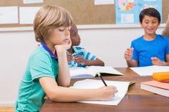 Leuke leerlingen die bij bureau in klaslokaal schrijven Stock Foto's