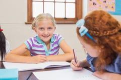 Leuke leerlingen die bij bureau in klaslokaal schrijven Royalty-vrije Stock Afbeelding