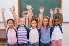 Leuke leerlingen die bij camera in klaslokaal glimlachen Stock Afbeeldingen