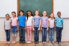 Leuke leerlingen die bij camera in klaslokaal glimlachen Stock Foto's