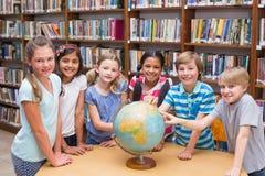 Leuke leerlingen die bol in bibliotheek bekijken Stock Afbeeldingen