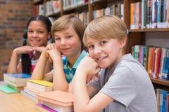 Leuke leerlingen die camera in bibliotheek bekijken Stock Afbeeldingen