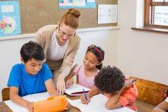Leuke leerlingen die hulp van leraar in klaslokaal krijgen Stock Foto