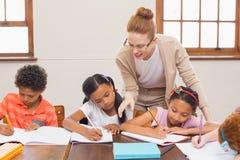 Leuke leerlingen die hulp van leraar in klaslokaal krijgen Stock Foto's