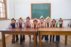 Leuke leerlingen die in klaslokaal glimlachen royalty-vrije stock afbeeldingen
