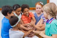 Leuke leerlingen die in klaslokaal glimlachen Stock Foto