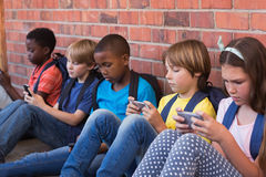 Leuke leerlingen die mobiele telefoon met behulp van stock foto