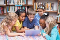 Leuke leerlingen die tablet in bibliotheek bekijken Stock Afbeeldingen