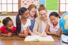 Leuke leerlingen en leraar die bij camera in klaslokaal glimlachen Stock Foto