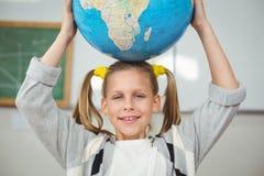 Leuke leerlings in evenwicht brengende bol op hoofd in een klaslokaal Royalty-vrije Stock Afbeeldingen