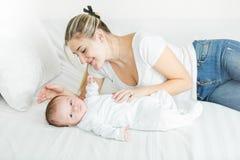 Leuke 3 maanden oud baby die op bed met jonge glimlachende moeder liggen Royalty-vrije Stock Fotografie