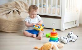 Leuke 10 maanden oud peuterjongen het spelen met stuk speelgoed auto op vloer bij slaapkamer Stock Fotografie