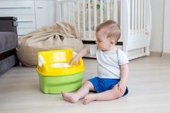 Leuke 10 maanden oud van de babyjongen sittin op vloer en het spelen met toiletpot Stock Foto's