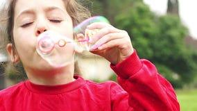 Leuke meisje blazende zeepbels in langzame motie stock footage
