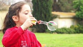 Leuke meisje blazende zeepbels in langzame motie stock video